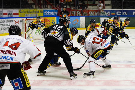 Sodertalje, Sweden - January 15, 2017: Face-off referee putting a puck between two ice hockey players in Ice hockey match in hockeyallsvenskan between SSK and MODO in the sports complex Scaniarinken 에디토리얼