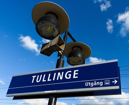 Tullinge, Sweden - August 12, 2015: Tullinge train station with the station sign, speaker, sign show exit direction to bus