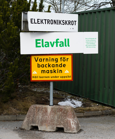 Salem, Sweden - Mars 5: Waste sorting at SRV recycling center in Salem, sign with electrical waste. electronic scrap and sign with text: warning of a reversing vehicle, keep children under supervision Editorial