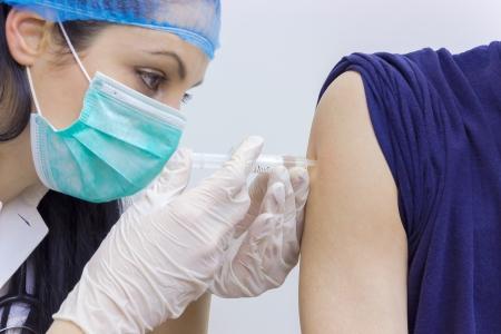 ESQUEMA DE VACUNACION: Un médico joven que da a un paciente una vacuna, la fotografía
