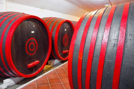poorly: Old wooden barrels for wine storage in a poorly lit basement, photography