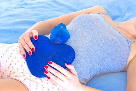 A young woman holding a water bottle on her stomach to alleviate stomach problems, photography Stock Photo - 18342986