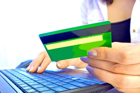 Young woman holding credit card on laptop for online shopping, photography