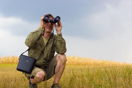 binoculars view: Young man with binoculars watching birds in nature, Man with binoculars, photography Stock Photo