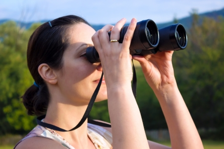 Young woman with binoculars watching birds in nature, Birdwatching, photography Banque d'images