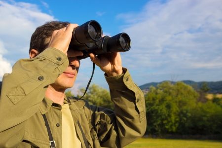 Young man with binoculars watching birds in nature, Man with binoculars, photography Banque d'images