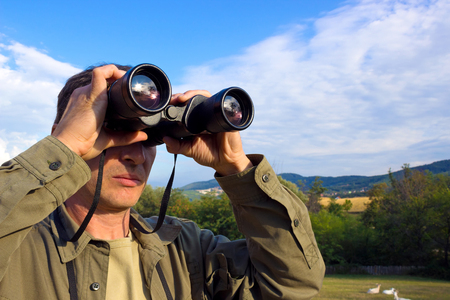Young man with binoculars watching birds in nature, Man with binoculars, photography Banco de Imagens
