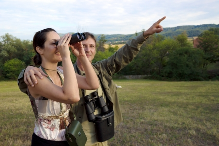 Couple with binoculars watching birds in nature, Birdwatching with binoculars, photography