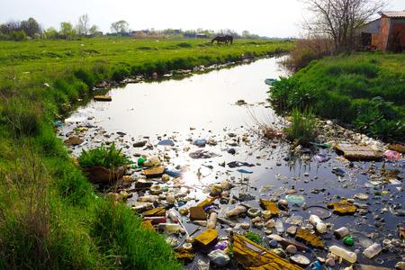 Rivier die is vervuild met diverse vuilnis en afval, vervuilde rivieren, fotografie