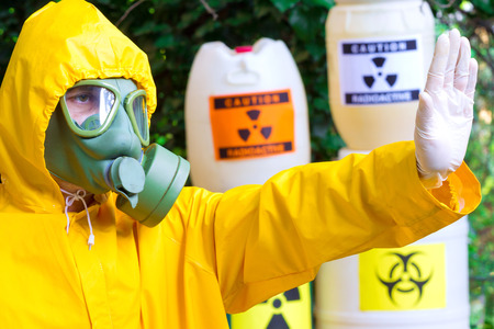 radiation warning sign: Risk of radiation ; Chemist in protective clothing with gas mask gives a warning sign,photography