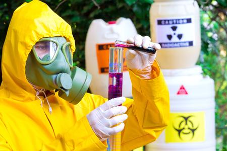 sustancias toxicas: Pruebas de sustancias tóxicas; Químico en ropa de protección con máscara de gas examinar supsance tóxico, fotografía