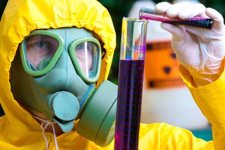 sustancias toxicas: Las sustancias tóxicas; Químico en ropa de protección con máscara de gas examinar supsance tóxico, fotografía