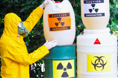 radio active: Work with hazardous materials ; Chemist with the gas mask and the protective suit the storing of radio active waste,photography Stock Photo
