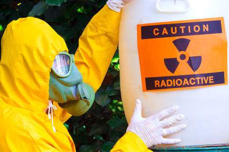 safeness: Radioactive waste ; Chemist with the gas mask and the protective suit the storing of radio active waste,photography Stock Photo
