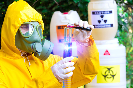 Total contamination ; Chemist in protective clothing with gas mask  examining toxic supsance,photography