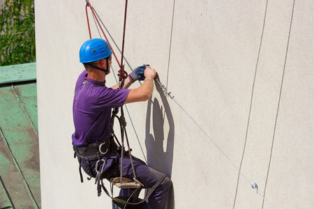 fall arrest: Works on skyscraper ; Specially equipped worker performs height work,photography