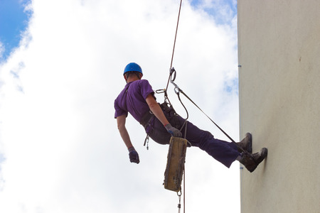 fall arrest: Climbing on the wall skyscrapers ; Specially equipped worker performs height work,photography Stock Photo