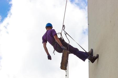 climbing: Escalada en los rascacielos de pared; Trabajador especialmente equipados realiza trabajos de altura, la fotograf�a