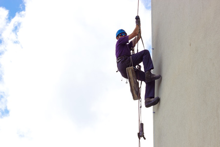Climber on skyscraper ; Specially equipped worker performs height work,photography photo