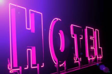 illuminated: Hotel neon sign ; Illuminated advertising for the hotel with light effects Stock Photo