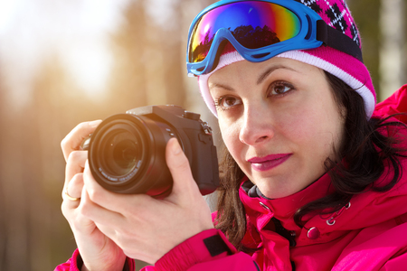 winter sports: Winter sports photographing ; A beautiful woman with a camera photographed winter sports