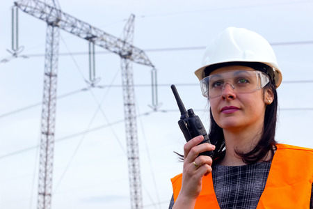 ingeniero electrico: ingeniero de distribución eléctrica que habla en un walkie-talkie; Ingeniero supervisor femenina para la electrificación mediante walkie-talkies, cerca de la línea de transmisión