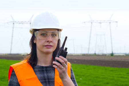 construction equipment: Female engineer electrician ; Supervising female engineer for electrification using walkie- talkies near the transmission line