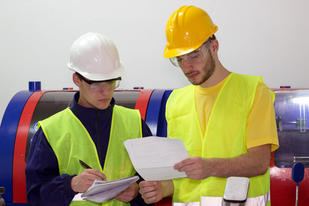 Two young mechanical workers ; Two young engineers are studying work plans