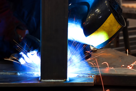 Arc welding of metals ; Welder with protective mask is working on metal welding