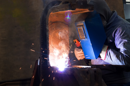 Welding of steel profiles ; Welder with protective mask is working on metal welding
