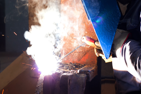 Glittering light of welding machine ; Welder with protective mask is working on metal welding