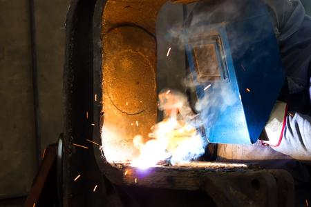Worker welder in the metal industry ; Welder with protective mask is working on metal welding