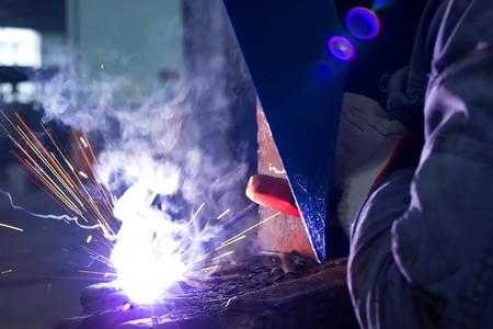 Welder welded metal constructions ; Welder with protective mask is working on metal welding Reklamní fotografie