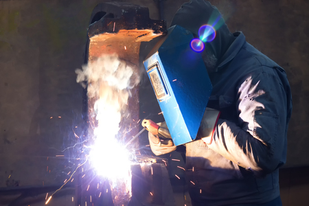 Welding of metal structures ; Welder with protective mask is working on metal welding