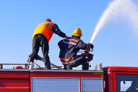 Firefighters in the fire fighting action / Firefighter with a water cannon extinguishes a fire