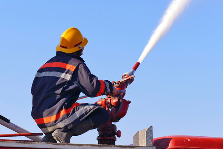 Firefighter on a water cannon / Firefighter with a water cannon extinguishes a fire