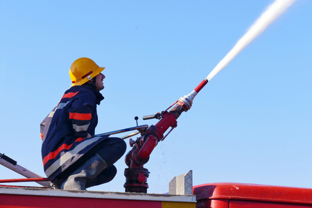 Fire fighting with water cannon /Firefighter with a water cannon extinguishes a fire