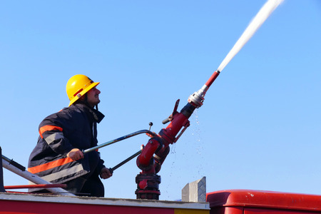 Firefighter with a water cannon / Firefighter with a water cannon extinguishes a fire Banco de Imagens