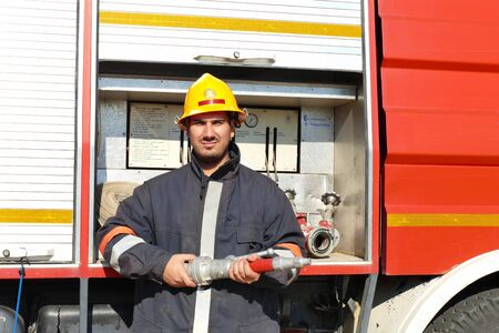 Firefighter in full gear / Fireman stands in front of a fire truck