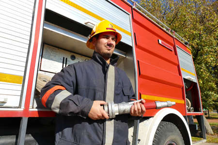 Firefighter with a hose / Fireman stands in front of a fire truck