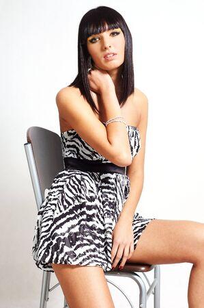 elegante brunette vrouw zittend op een stoel Stockfoto
