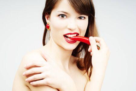 mooie vrouw zetten een chili peper in haar mond