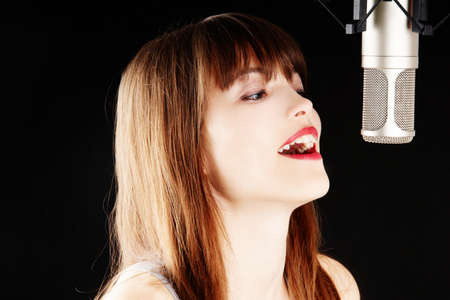 girl singing to the microphone in a studio Stock Photo