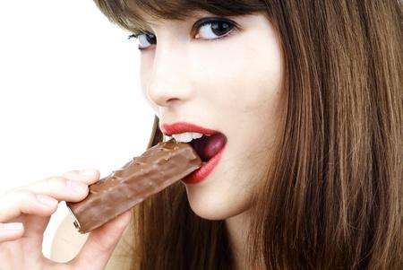beautiful girl biting a bar of chocolate in a sexy way Stock Photo - 9069026