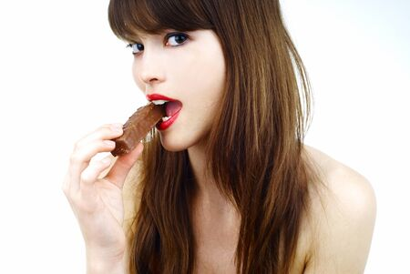 beautiful girl biting a bar of chocolate photo