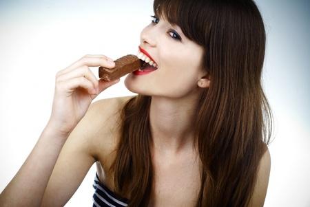 mooi meisje bijten een bar van chocolade in een sexy manier