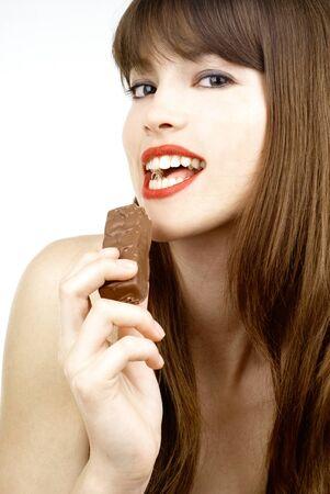 beautiful girl biting a bar of chocolate in a sexy way photo