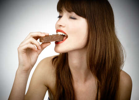 beautiful girl biting a bar of chocolate in a sexy way photo