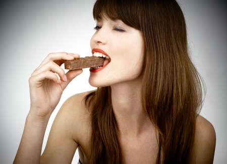 beautiful girl biting a bar of chocolate in a sexy way Stock Photo