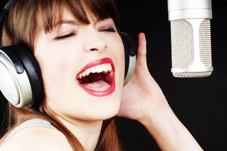 expressive woman singing to the microphone photo